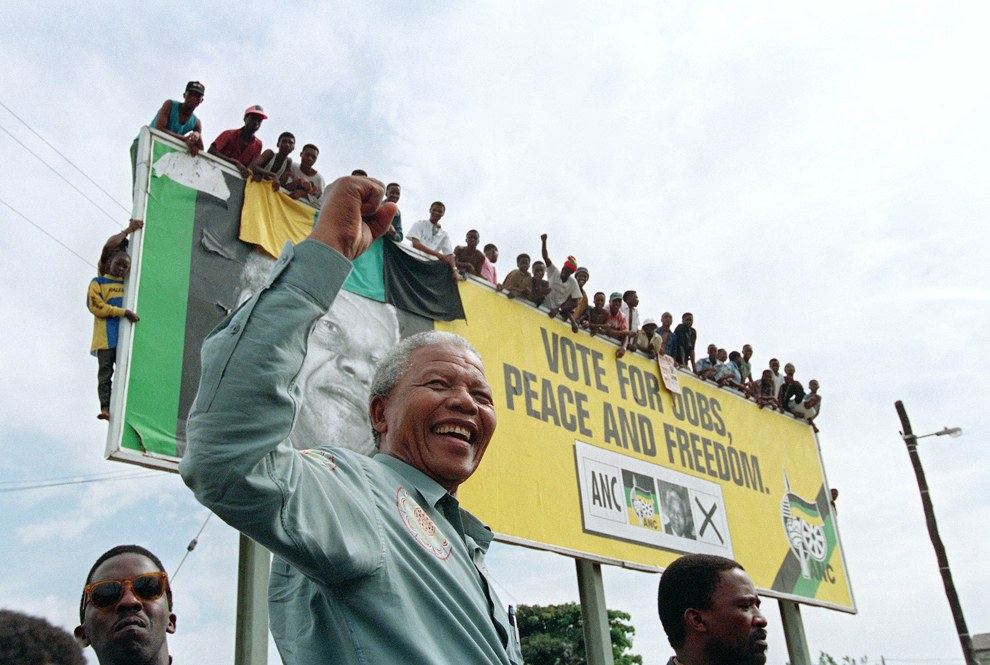 Preşedintele Congresului Naţional African (CNA), Nelson Mandela, salută tinerii suporteri care îl aşteaptă suiţi pe un panou electoral din afara oraşului Durban, în Africa de Sud, sâmbătă, 16 aprilie 1994.