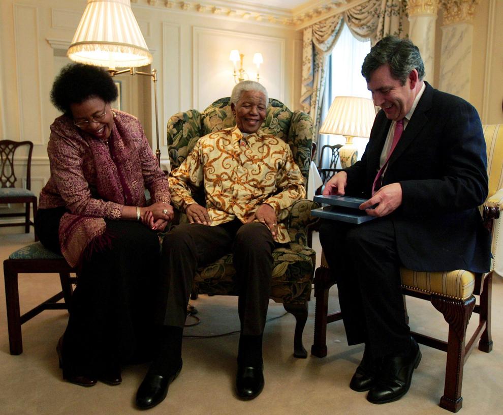 Premierul britanic, Gordon Brown (D), primeşte o fotografie realizată în timpul vizitei sale de anul trecut în Africa de Sud, în timpul unei întâlniri cu fostul preşedinte sud-african, Nelson Mandela, şi cu soţia acestuia, Graca Machel, în Londra, miercuri, 2 februarie 2005.