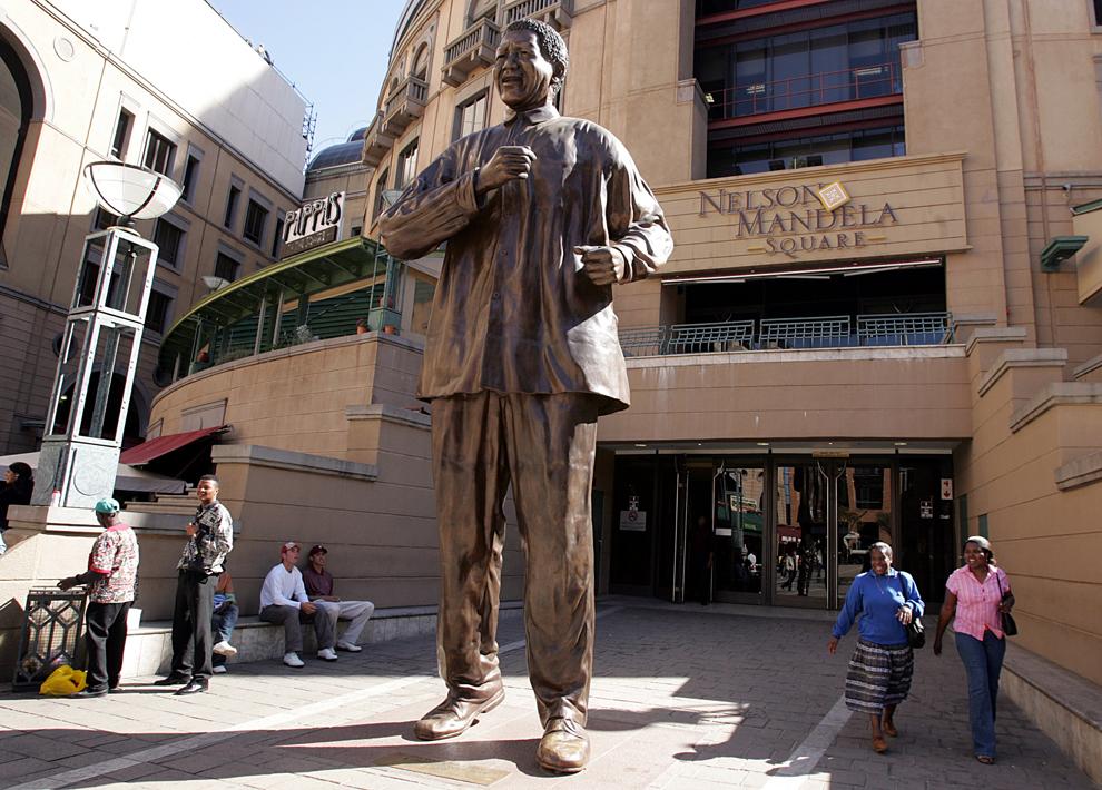 Sud-africani trec pe lângă o statuie a fostului preşedinte sud-african, Nelson Mandela, în Johannesburg, marţi, 31 mai 2005.