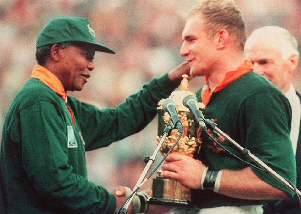 Francois Pienaar (D), căpitanul echipei de rugby a Africii de Sud, este felicitat de către preşedintele Africii de Sud, Nelson Mandela (S), după victoria echipei sale în faţa Noii Zeelande, în finala Cupei Mondiale de Rugby, în Johannesburg, sâmbătă, 25 iunie 1995.