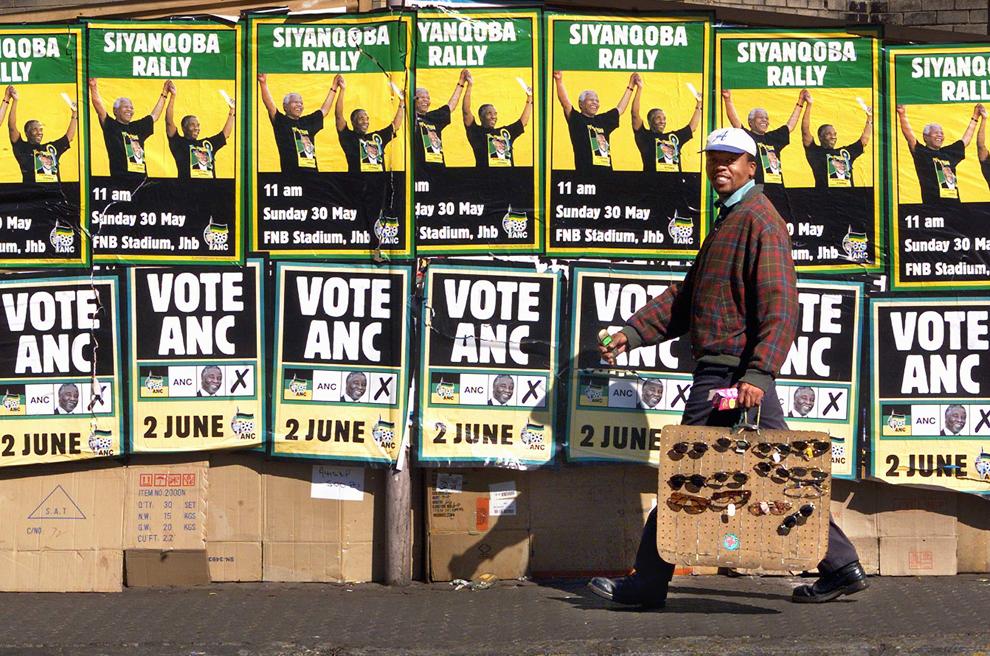 Un vânzător ambulant de ochelari trece pe lângă un zid acoperit cu afişe ale Congresului Naţional African (CNA), în centrul oraşului Johannesburg, marţi, 1 iunie 1999.