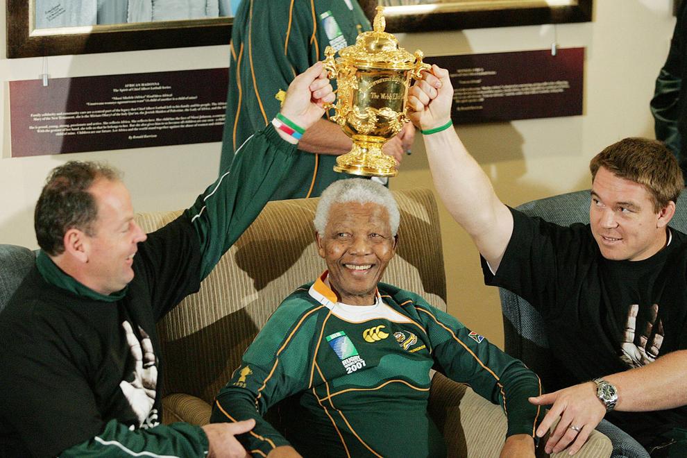 Fostul preşedinte sud-african, Nelson Mandela (C), pozează alături de antrenorul selecţionatei de rugby a Africii de Sud, Jake White (S), căpitanul acesteia, John Smith (D), şi trofeul Webb-Ellis, la reşedinţa liderului anti-apartheid din Johannesburg, sâmbătă, 27 octombrie 2007. Africa de Sud a căştigat trofeul Webb-Ellis învingând în finală selecţionata Angliei.