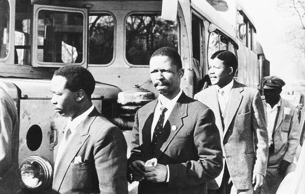 O fotografie nedatată îi înfăţişează pe Nelson Mandela (D3), lider al Congresului Naţional African (CNA), Patrick Molaoa şi Robert Resha, acuzaţi de trădare de către Uniunea Sud-Africană, îndreptându-se spre tribunalul unde urmează a fi judecaţi, în Johannesburg, Africa de Sud.