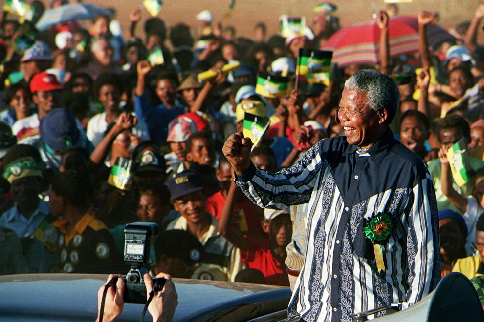 Preşedintele Congresului Naţional African, Nelson Mandela, salută mulţimea în timp ce intră în ghetoul Roodepan din Kimberley, cu ocazia unui miting electoral, joi, 24 februarie 1994.