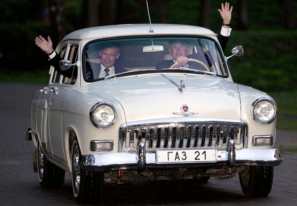 Preşedintele american, George W. Bush (D) face cu mâna în timpul unei plimbări cu maşina Volga 1956 deţinută de preşedinte rus,  Vladimir Putin (S)  în Moscova, duminică, 8 mai 2005.