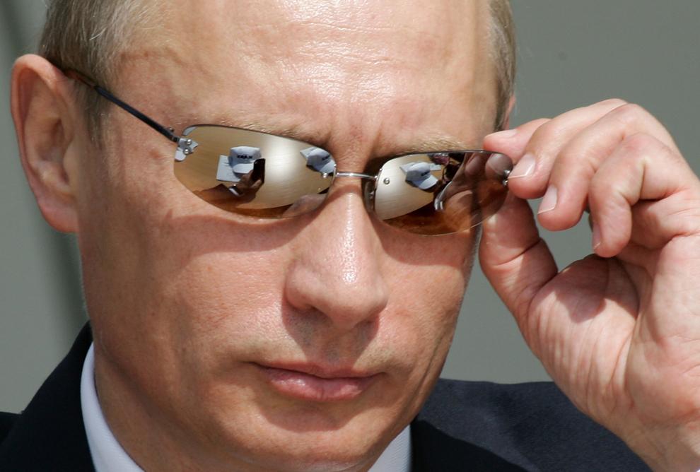 Preşedintele Rusiei,  Vladimir Putin îşi ajustează ochelarii de soare în timpul expoziţiei internaţionale Maks-2005, în Zhukovsky, aproximativ 50 km distanţă de Moscova, marţi, 16 august 2005.