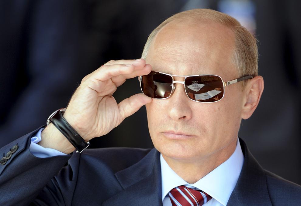 Prim-ministrul rus Vladimir Putin îşi aranjează ochelarii de soare, în timpul spectacolului aerian MAKS-2011, în Zhukovsky, în afara Moscova, miercuri, 17 august 2011.