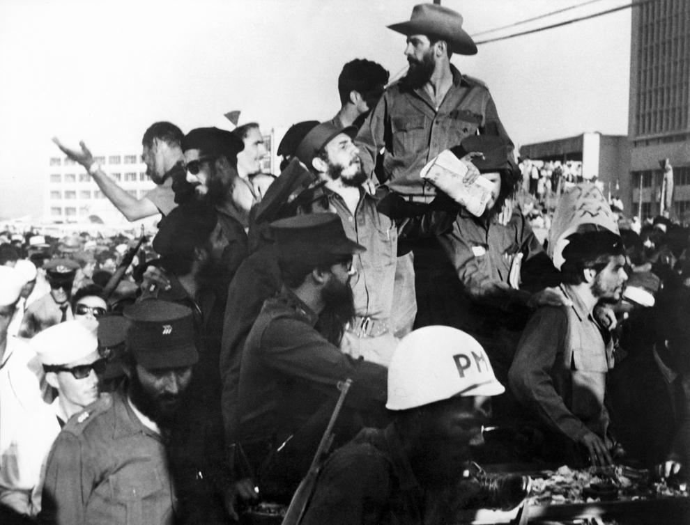 """Liderul rebelilor cubanezi Fidel Castro (C) alături de membrii mişcarii de gherilă  """"26th of July Movement"""", Camilo Cienfuegos (cu pălărie) şi Ernesto Che Guevara (D cu beretă), salută publicul la intrarea în Havana după victoria împotriva forţelor dictatorului cubanez Fulgencio Batista, joi, 8 ianuarie 1959."""