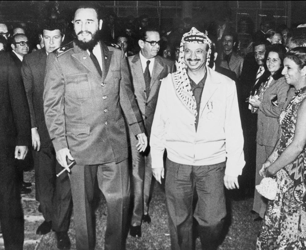 Preşedintele Autorităţii Naţionale Palestiniene (ANP), Yasser Arafat (D) merge alături de liderul cubanez, Fidel Castro în timpul unei vizite în Cuba, în decembrie 1974.