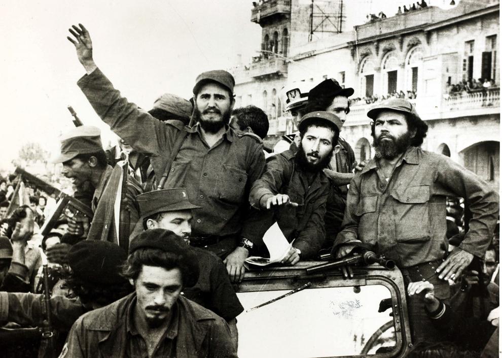 Liderul rebelilor cubanezi, Fidel Castro îşi ridică pumnul la intrarea în Havana alături de bodyguard-ul său.