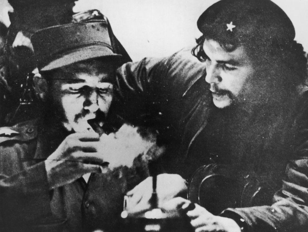 """Revoluţionarul cubanez, Fidel Castro (S) işi aprinde un trabuc lângă revoluţionarul argentinian Erneso """"Che"""" Guevara (1928 - 1967), în munţii Sierra Maestra din Cuba, circa 1956."""