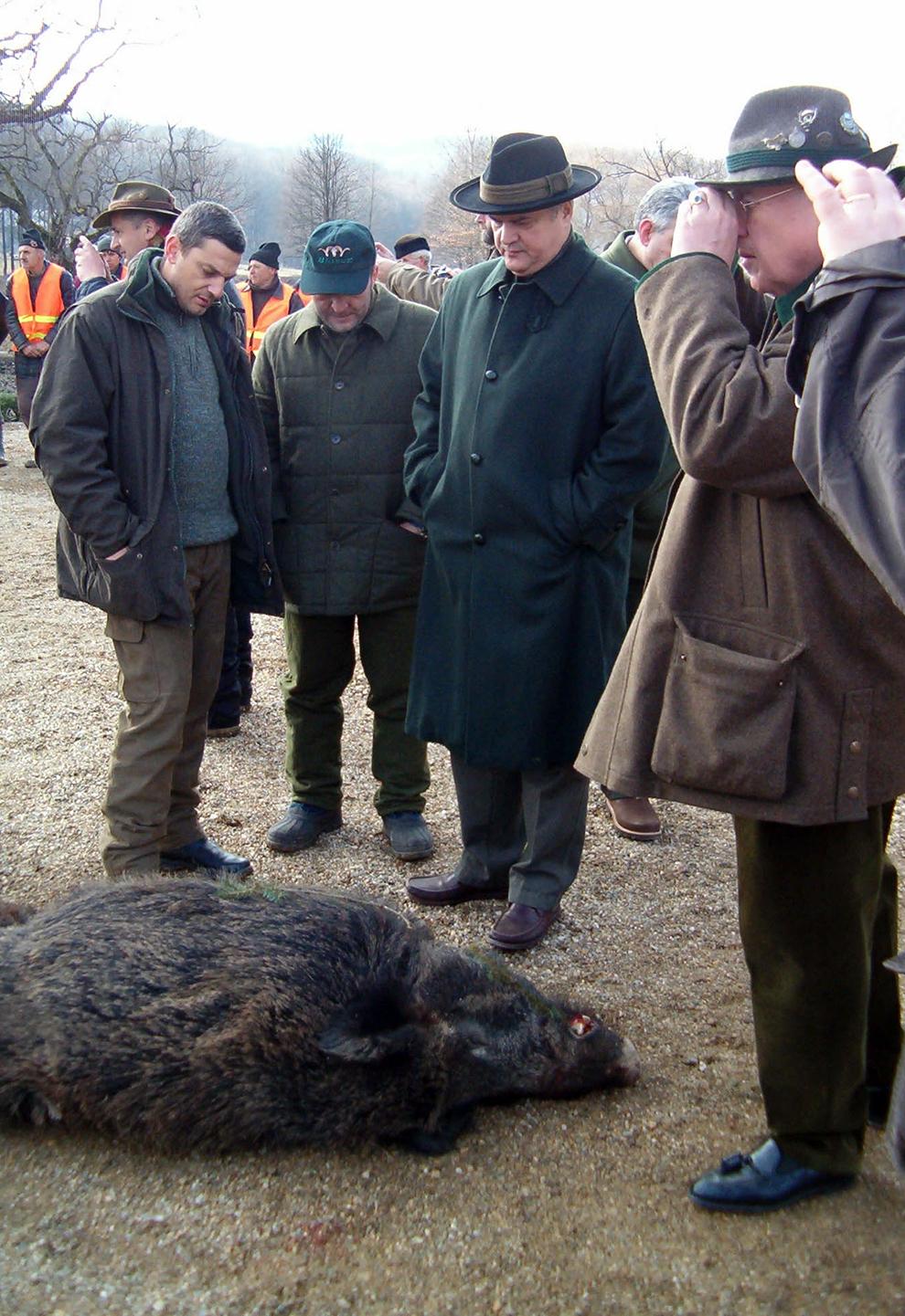 Adrian Năstase (C) se uită la un porc mistreţ omorât în timpul unei partide de vânătoare, organizate de omul de afaceri Ion Ţiriac, pe un domeniu situat lângă localitatea Bâlc, din judeţul Bihor, luni, 24 ianuarie 2005.