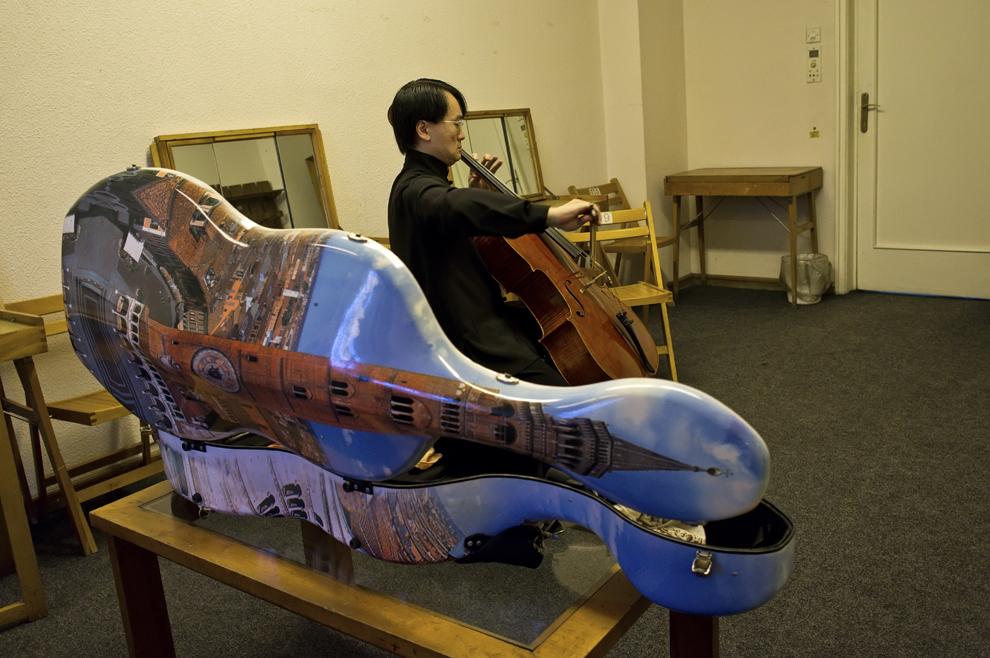 Virtuozul Jian Wang face ultimele ajustări înaintea unui program ce a conţinut Dvorak şi Sostakovici. Tocul violoncelului său, cu Big Ben, este recognoscibil, astfel Jian fiind lesne de recunoscut şi din spate atunci când îl poartă pe umeri, 26 septembrie 2012, Festivalul RadiRo, Bucureşti.