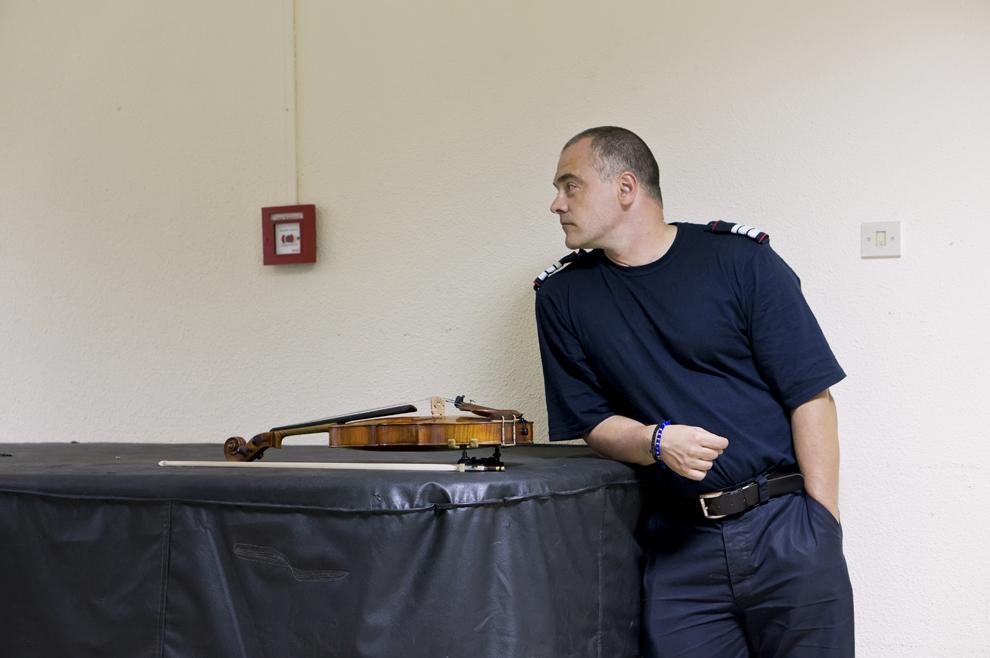Un jandarm stă lângă o vioară, înainte de concertul inaugural al primei ediţii a festivalului RadiRo, 23 septembrie 2012, Bucureşti.