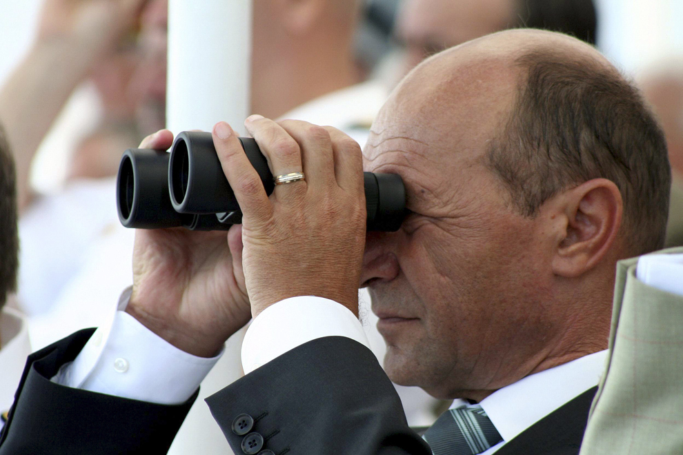 Preşedintele României, Traian Băsescu, urmăreşte, cu binoclul, exerciţiile demonstrative ale navelor Marinei Militare, în Constanţa, miercuri, 15 august 2007.