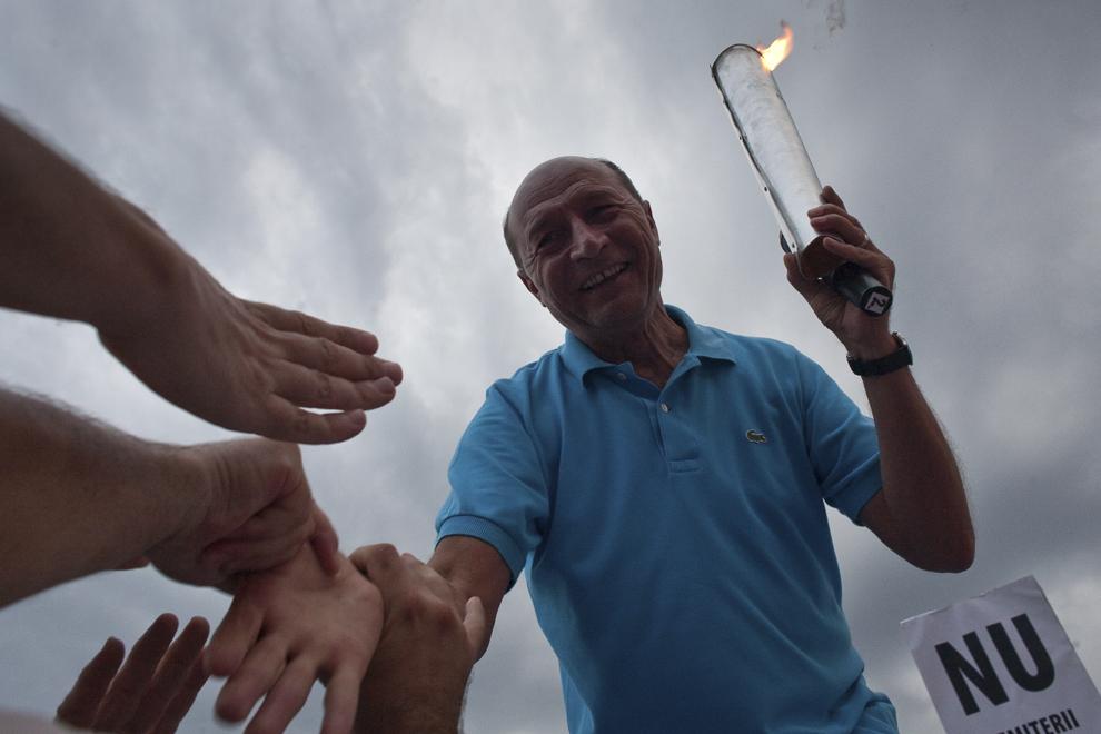 """Preşedintele suspendat al României, Traian Băsescu, susţine un discurs cu """"flacăra democraţiei"""" în mâna, primită de la susţinători, în timpul unui miting pentru Susţinerea Democraţiei prin Neparticiparea la Referendum organizat de Partidul Democrat Liberal, în Piaţă George Enescu din Bucureşti, joi, 26 iulie 2012."""