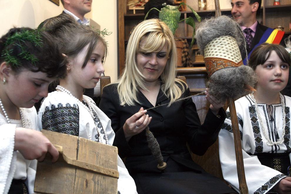 """Ministrul Turismului, Elena Udrea, toarce lana, in timpul vizitei efectuate in Bucovina pentru promovarea proiectului """"Pastele in Bucovina"""", la Gura Humorului, vineri, 10 aprilie 2009."""