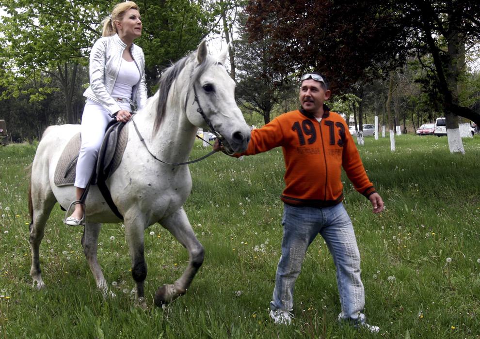 """Ministrul Turismului, Elena Udrea, calareste un cal, la herghelia de la Mangalia, sambata, 2 mai 2009. Elena Udrea a vizitat herghelia de la Mangalia, unde a calarit pentru cateva minute, moment in care s-a adresat presei si oficialilor locali: """"Dati-va la o parte, ca acum sunt chiar pe cai mari!""""."""