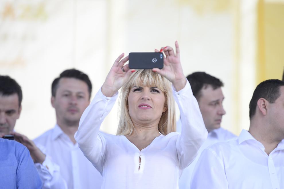 Elena Udrea fotografiaza cu telefonul mobil, in timpul unui protest fata de introducerea accizei suplimentare la combustibil, in Piata George Enescu din Capitala, sâmbata, 15 martie 2014. Mitingul este organizat de Partidul Miscarea Populara (PMP).
