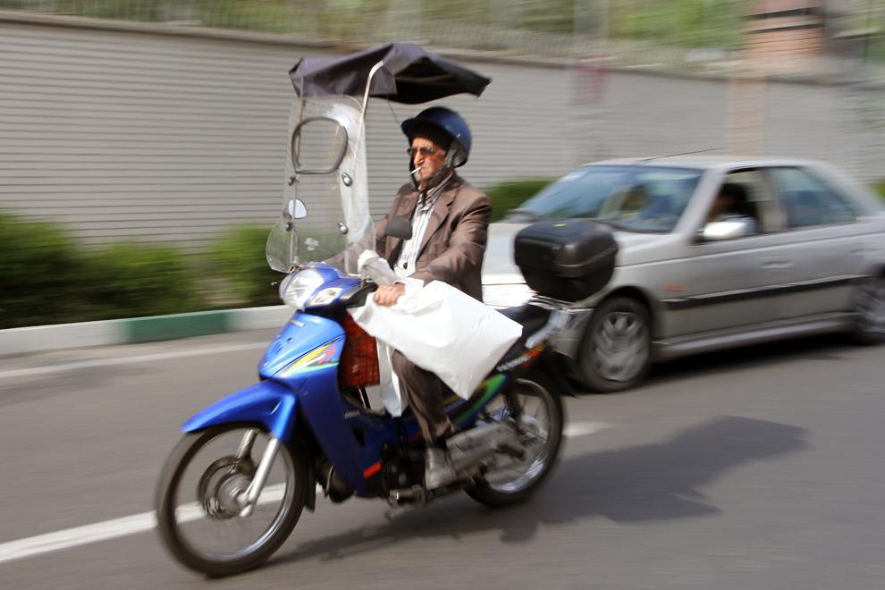 Un bărbat circulă cu o motocicletă pe o stradă din Teheran.