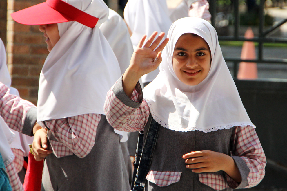 O elevă iraniană în uniformă face cu mâna turiştilor care vizitează complexul arheologic Persepolis.