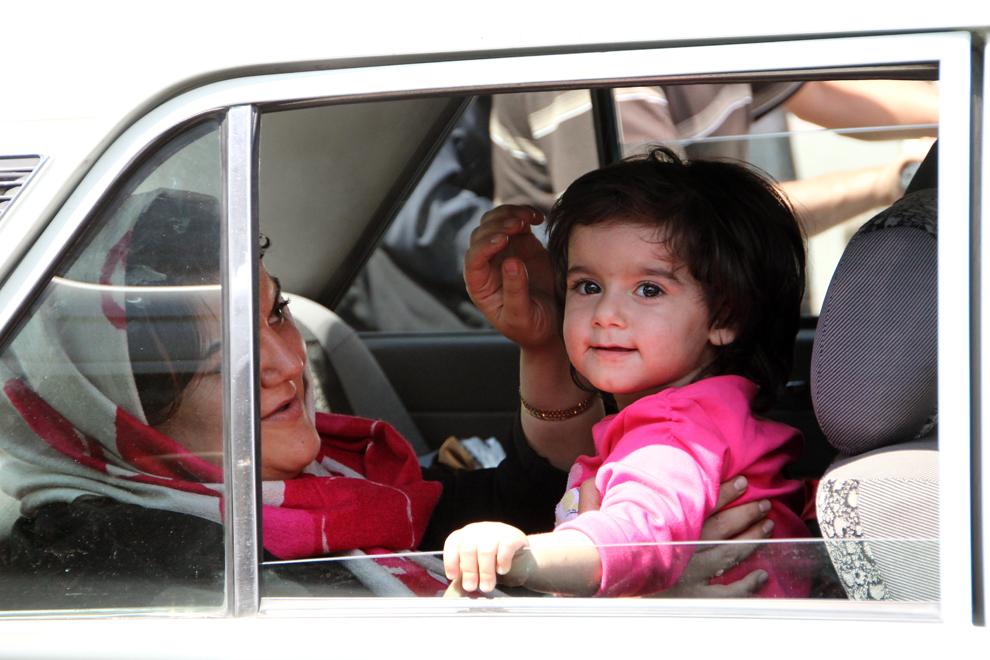 O mamă iraniană îşi mângâie copilul într-un taxi la o intersecţie din Teheran.