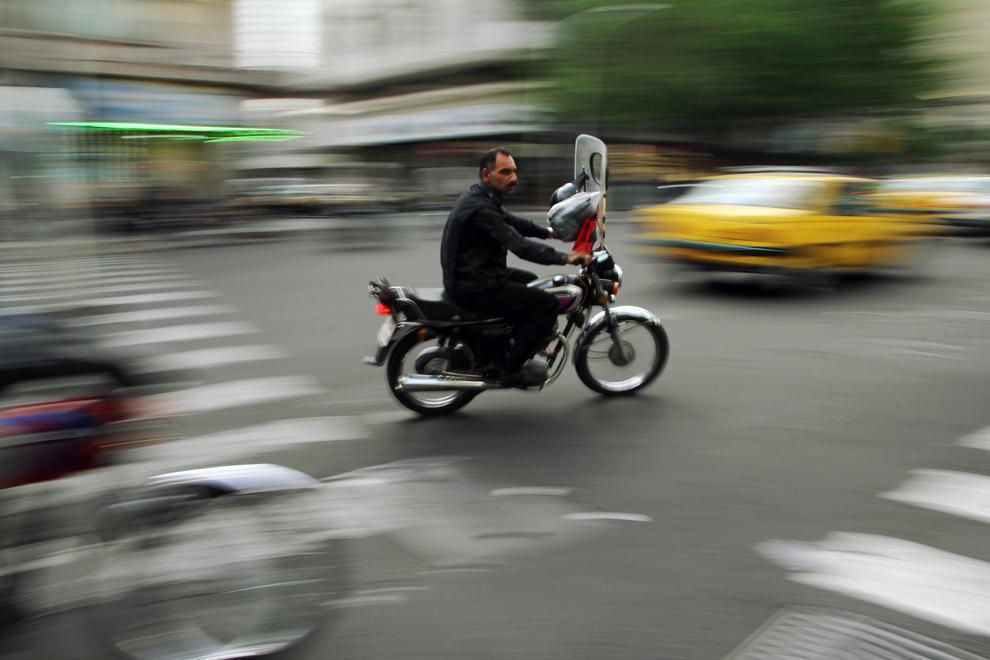 Un motociclist conduce pe una din străzile din Teheran. In Iran se comercializează unele dintre cele mai ieftine produse petroliere, preţul litrului de motorină fiind de aproximativ 10 bani.