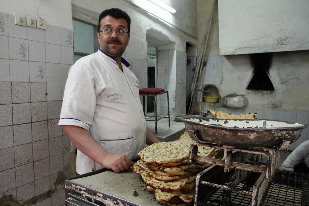 """Un bărbat produce pâine tradiţională într-o brutarie, în Teheran. Lipia tradiţională iraniană, denumită """"sangak"""", în traducere """"pâine pe pietre"""", poate ajunge până la un metru în diametru şi se vinde adeseori la kilogram."""