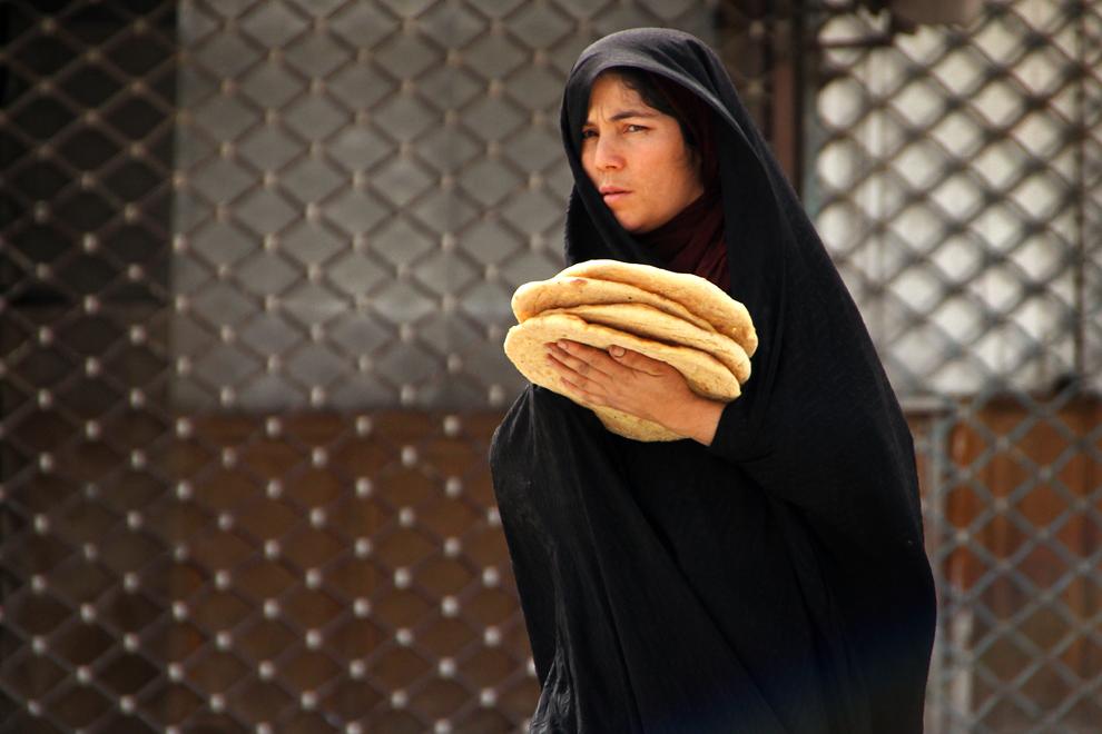 O femeie duce în braţe pâine proaspăt cumpărată. Pâinea tradiţională este foarte apreciată de iranieni, fiind considerată şi foarte bogată în fibre.