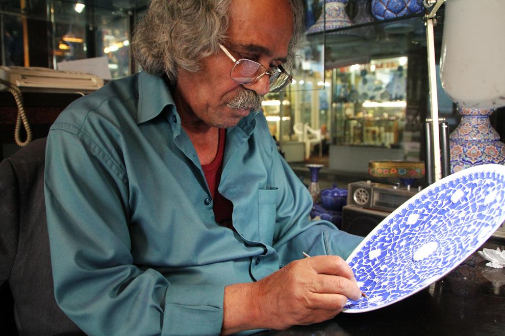 Un bărbat pictează în motive tradiţionale un vas din ceramică. Turiştii pot alege din bazar opere de artizanat ce pot fi pictate chiar pe loc.