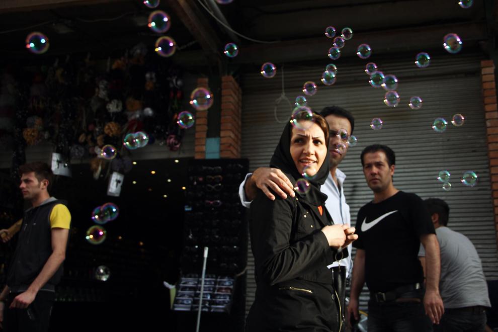 Tinerii iranieni, aici prin bazarul din Teheran, afişează adeseori şi ţinute mai puţin conservatoare.