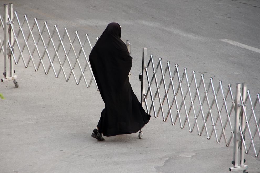 """O femeie traversează o strada în Teheran. Îmbrăcămintea tradiţională a femeii iraniene este """"chador""""-ul."""