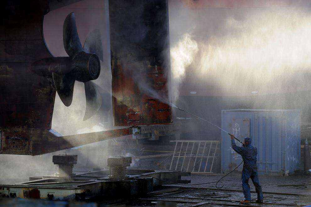 Un muncitor curăţă carcasa unui vas de pescuit într-un doc din Reykjavik, luni, 21 aprilie 2009.