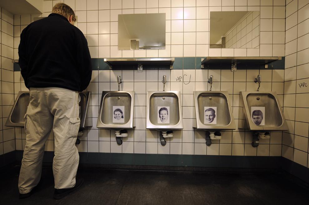 Un bărbat urinează în toaleta barului Sodoma din centrul capitalei Islandei, Reykjavík, unde fotografii ale foştilor bancheri care au părăsit ţara după izbucnirea crizei financiare au fost lipite de pişoare, vineri, 25 aprilie 2009.