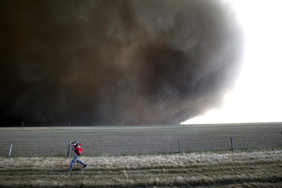 Un bărbat aleargă pe un câmp pentru a fotografia erupţia vulcanului Eyjafjallajokull, sâmbătă, 17 aprilie 2010.