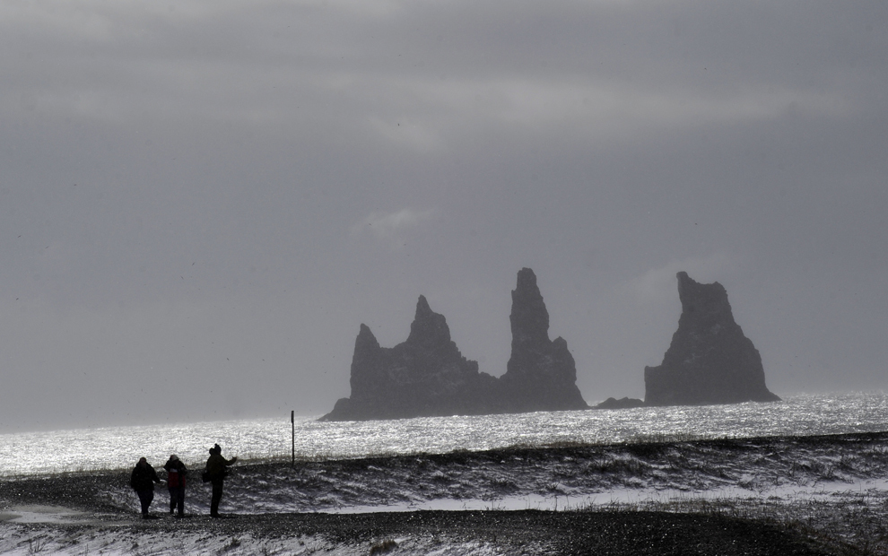 Trei turişti privesc stâncile uriaşe aflate pe coasta satului Vik, aflat la baza gheţarului Myrdalsjokull, care face parte din calota de gheaţă care acoperă vulcanul Katla, în Vik, joi, 22 aprilie 2010.