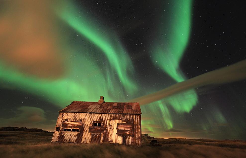 O fotografie realizată în octombrie 2010 înfăţişează aurora boreală deasupra unui hambar ruginit, în Hafnarfjšr, Islanda.