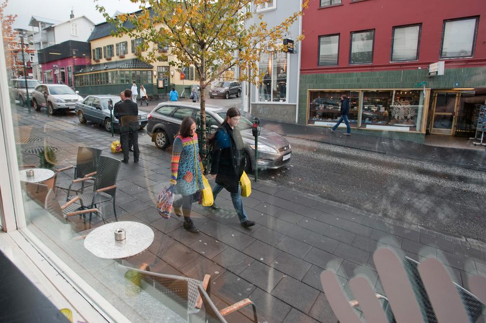 Pietoni, cărând pungi cu cumpărături, trec pe lângă o cafenea din Reykjavik, luni, 26 septembrie 2011.