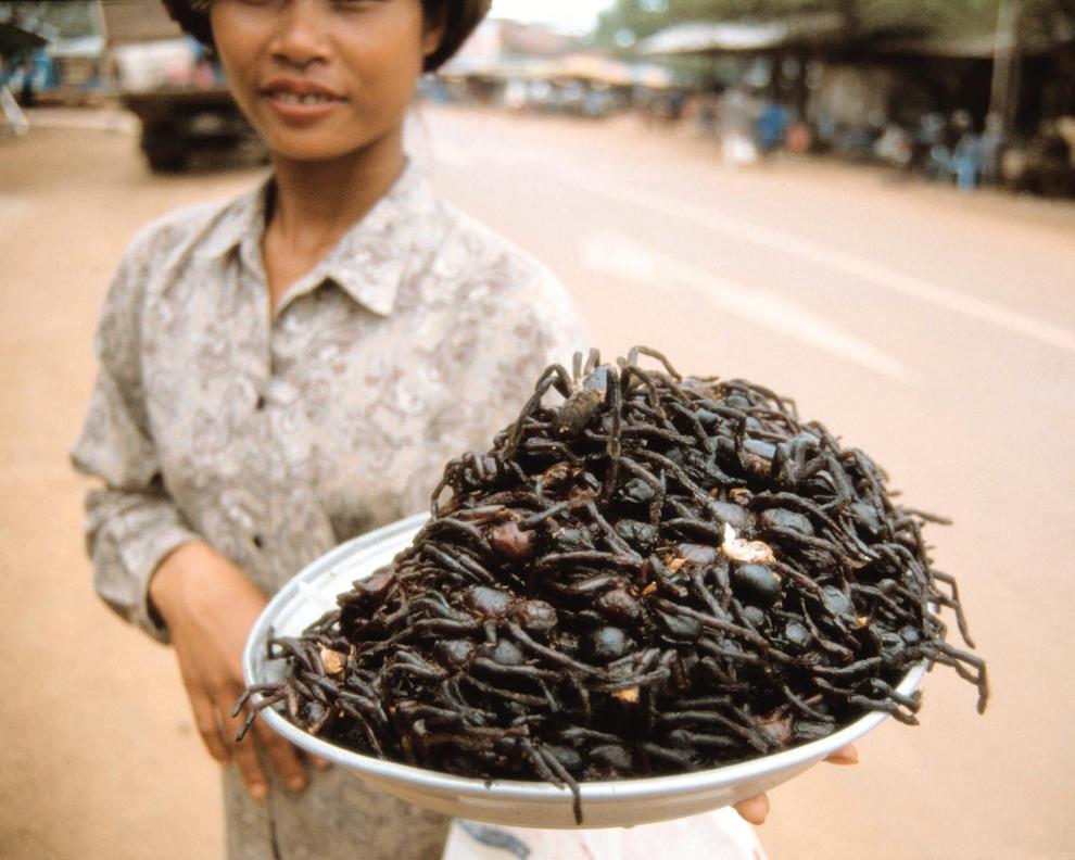 Un vânzator ambulant oferă spre vânzare tarantule prăjite în ulei cu usturoi, în Phnom Penh, miercuri, 9 octombrie 2002.