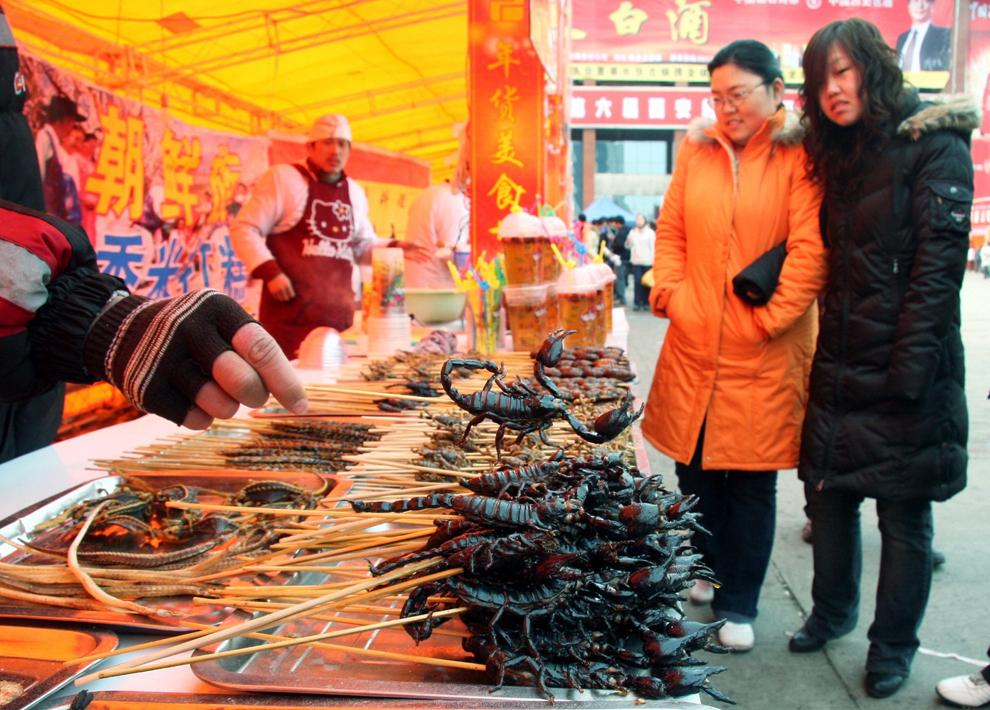 Două femei privesc de aproape păianjenii, scorpionii şi miriapodele vândute la un stand cu mâncare, în oraşul Xian din provincia Shanxi din vestul Chinei, joi, 24 ianuarie 2008.