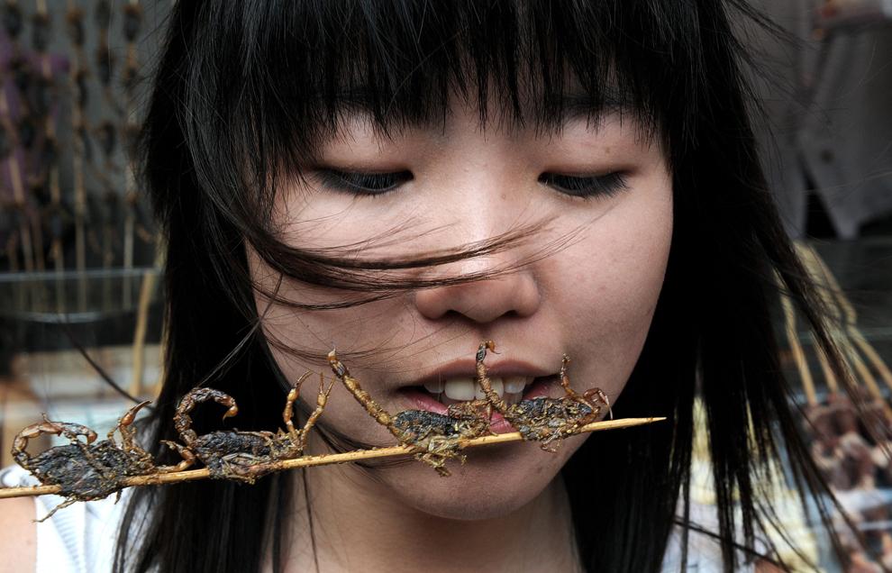 O turistă chineză din Shanghai mănâncă scorpioni pe băţ, vânduţi alături de viermi de mătase şi căluţi de mare într-o piaţă stradală din Beijing, miercuri, 23 iulie 2008.