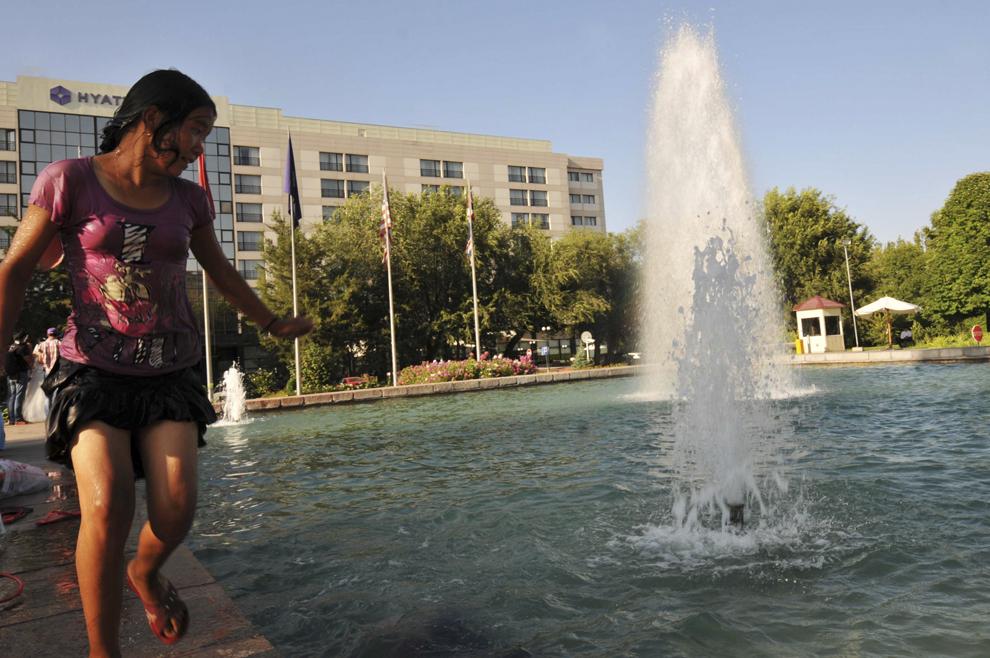 Copii fac baie într-o fântână arteziană, în capitala Kârgâzstanului, Bishkek, august 2013.