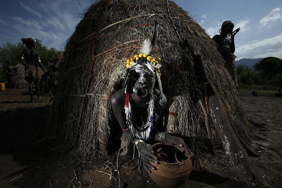Femeie din tribul Mursi de pe Valea râului Omo din sudul Etiopiei pozează la intrarea în coliba tradiţională din paie în care locuieşte.