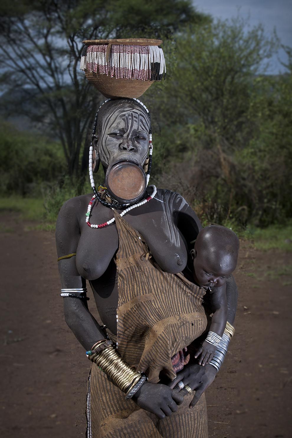 O femeie din tribul Mursi de pe Valea râului Omo din sudul Etiopiei pozează împreună cu copilul ei.