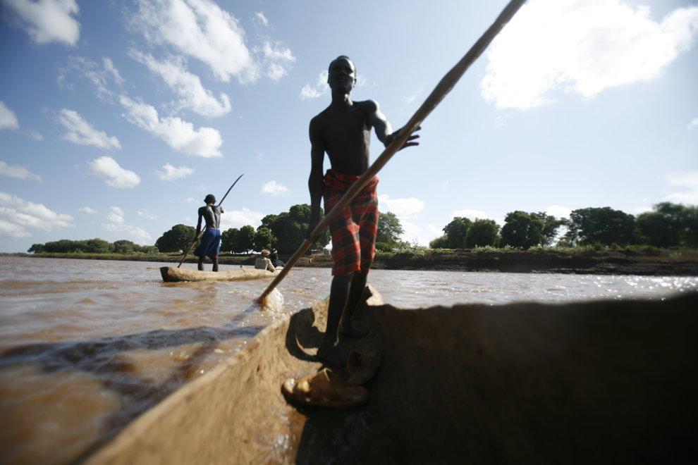 Membru al tribului Dassanech de pe Valea râului Omo din sudul Etiopiei îşi câştiga existenţa traversând localnici şi turişti de pe un mal pe altul al râului, într-o canoe dintr-un trunchi de copac scobit.