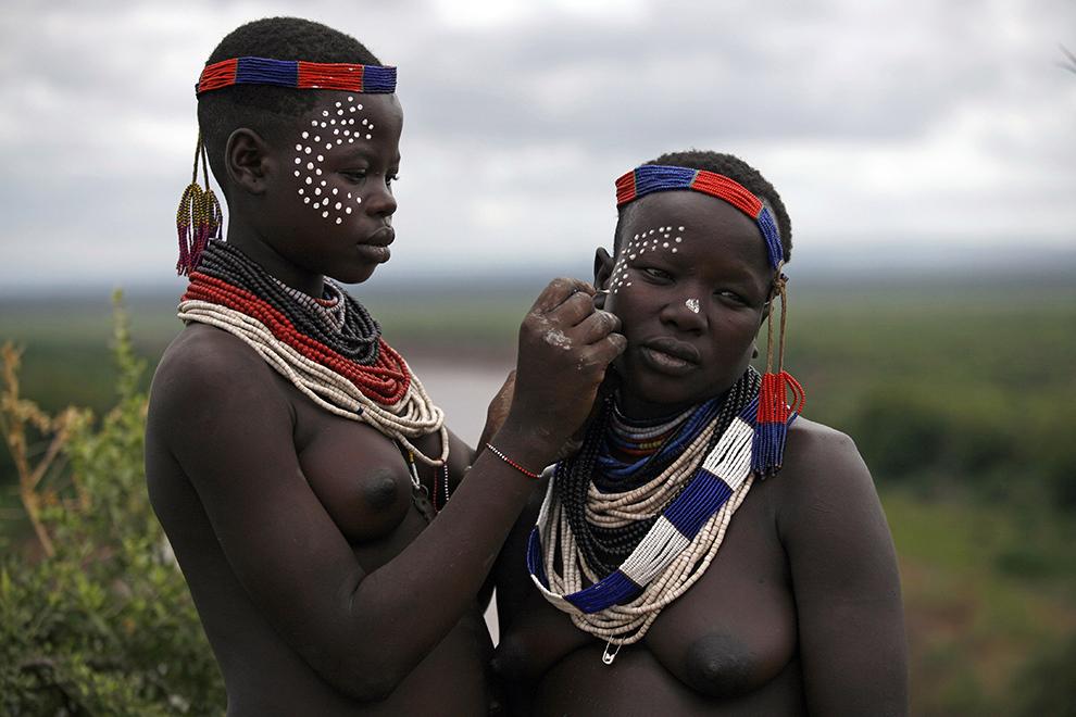 Femei din tribul Karo de pe Valea râului Omo din sudul Etiopiei îşi pictează reciproc pe faţa decoraţiuni tradiţionale.