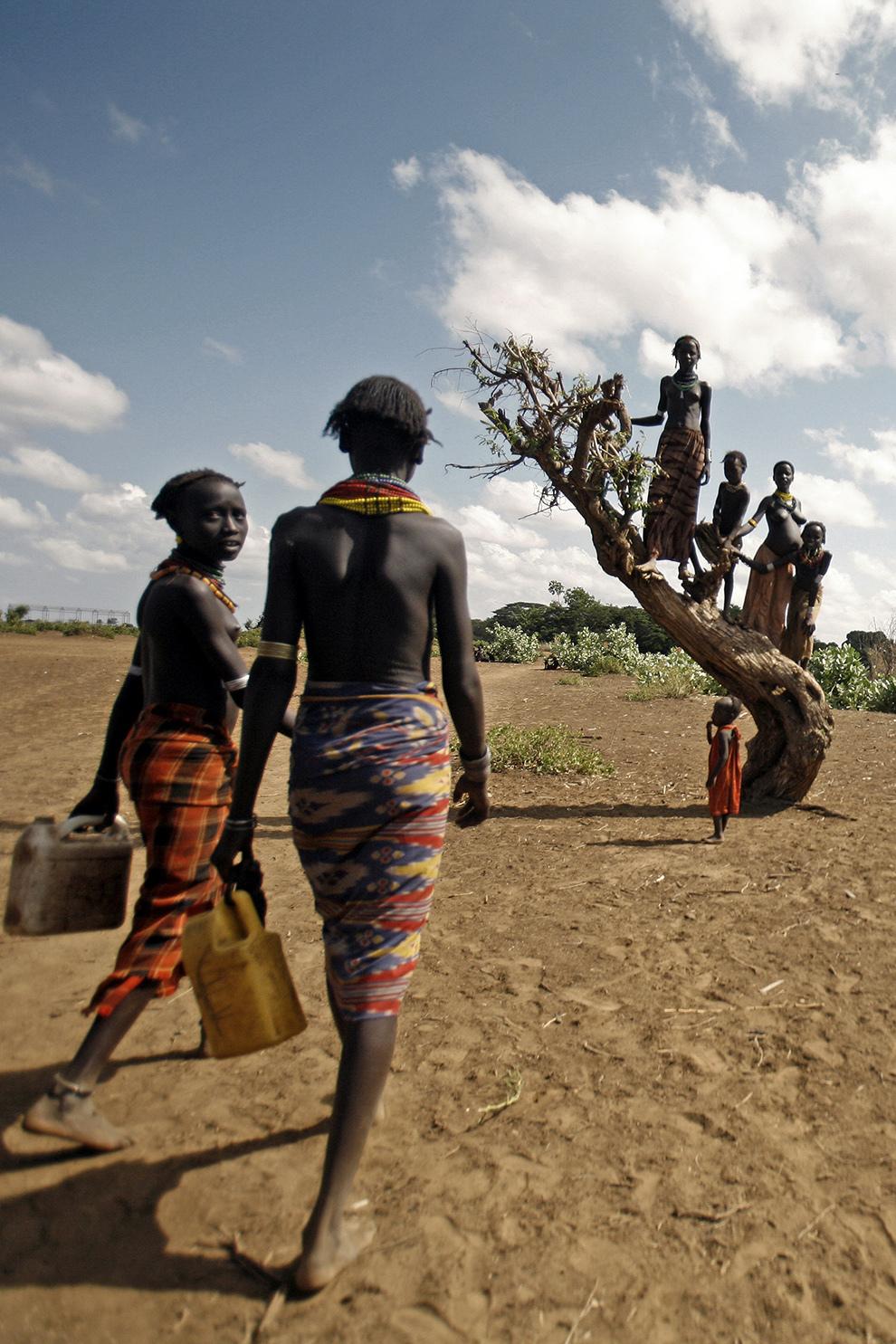Copii din tribul Dassanech de pe Valea râului Omo din sudul Etiopiei se urcă într-un copac pentru a le întâmpina pe cele două femei care se întorc de la râu cu recipiente umplute cu apa.