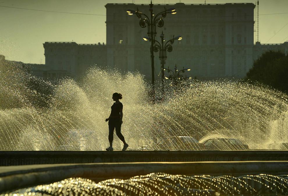 O femeie merge la apus prin zona fântânilor din faţa Palatului Parlamentului, construit în timpul dictaturii lui Nicolae Ceauşescu, în Bucureşti, duminică, 28 august 2005.