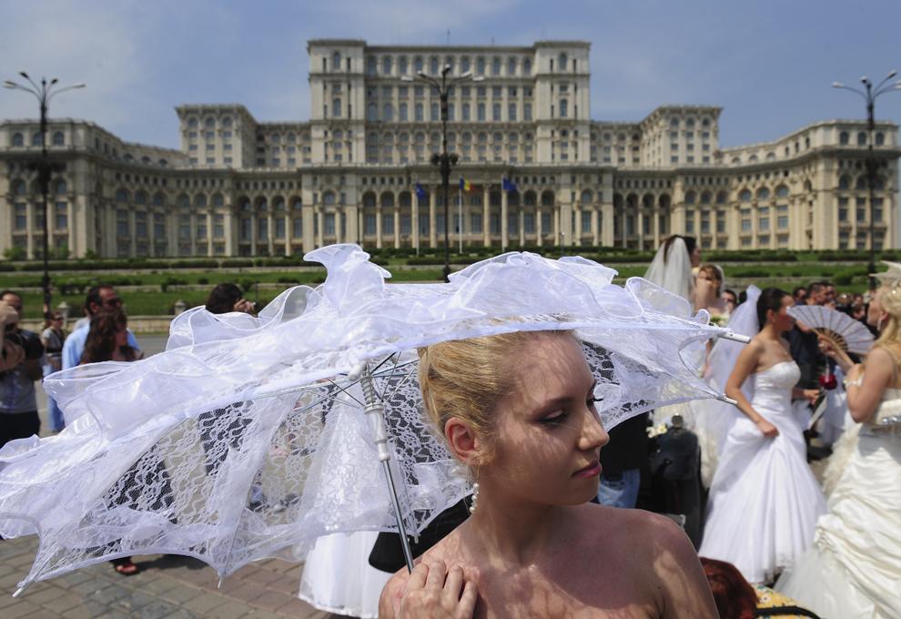 Femei purtând rochii de mireasă pozează în faţa Palatului Parlamentului din Bucureşti, în timpul evenimentului Bride Parade, duminică, 17 mai 2009.