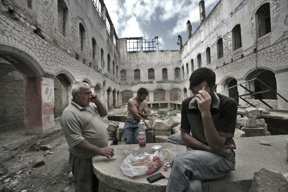 Un grup de muncitori se odihneşte în timpul pauzei de prânz în interiorul unei cladiri aflate în ruină din oraşul Shushi, joi, 18 septembrie 2008, în Nagorno-Karabah. Mai mult de trei sferturi dintre clădirile din Shushi au fost distruse în timpul războiului din Nagorno-Karabah.